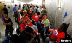 FILE - Protesters, mostly handicapped, line up outside the Senate Finance Committee hearing room hours ahead of a hearing on one of the Republicans' efforts to repeal Obamacare on Capitol Hill in Washington, Sept. 25, 2017.