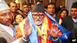 Nepal's newly elected Prime Minister Sushil Koirala waves to the media at the Constitution Assembly Hall in Katmandu, Nepal, Feb. 10, 2014.