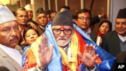 FILE - Nepal's newly elected Prime Minister Sushil Koirala waves to the media at the Constitution Assembly Hall in Katmandu, Nepal.
