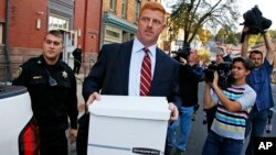 FILE - Former Penn State University assistant football coach Mike McQueary, center, leaves the Centre County Courthouse Annex in Bellefonte, Pa., Oct. 17, 2016. McQueary was awarded $7.3 million in his defamation and whistleblower lawsuit against Penn State over how it treated him for exposing child abuse at Penn State.