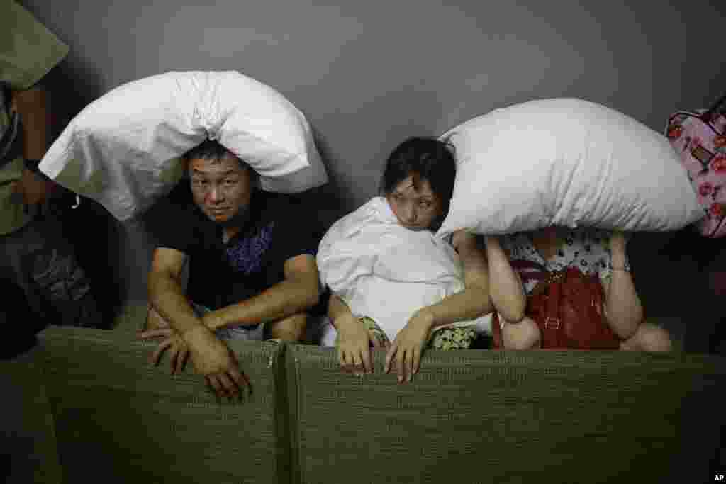 A family from San Jose, California, cover themselves with pillows as they sit on the concrete stairs in the service area of a resort after the designated area for shelter was destroyed by winds in Los Cabos, Mexico. Hurricane Odile raked the Baja California Peninsula with strong winds and heavy rains as locals and tourists in the resort area of Los Cabos began to emerge from shelters and assess the damage.