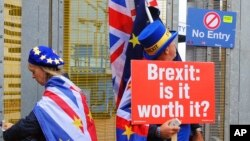 FILE - Anti-Brexit protesters stand outside the International Convention Center in Birmingham during a Conservative Party Conference at the ICC, in Birmingham, England, Oct. 2, 2018.