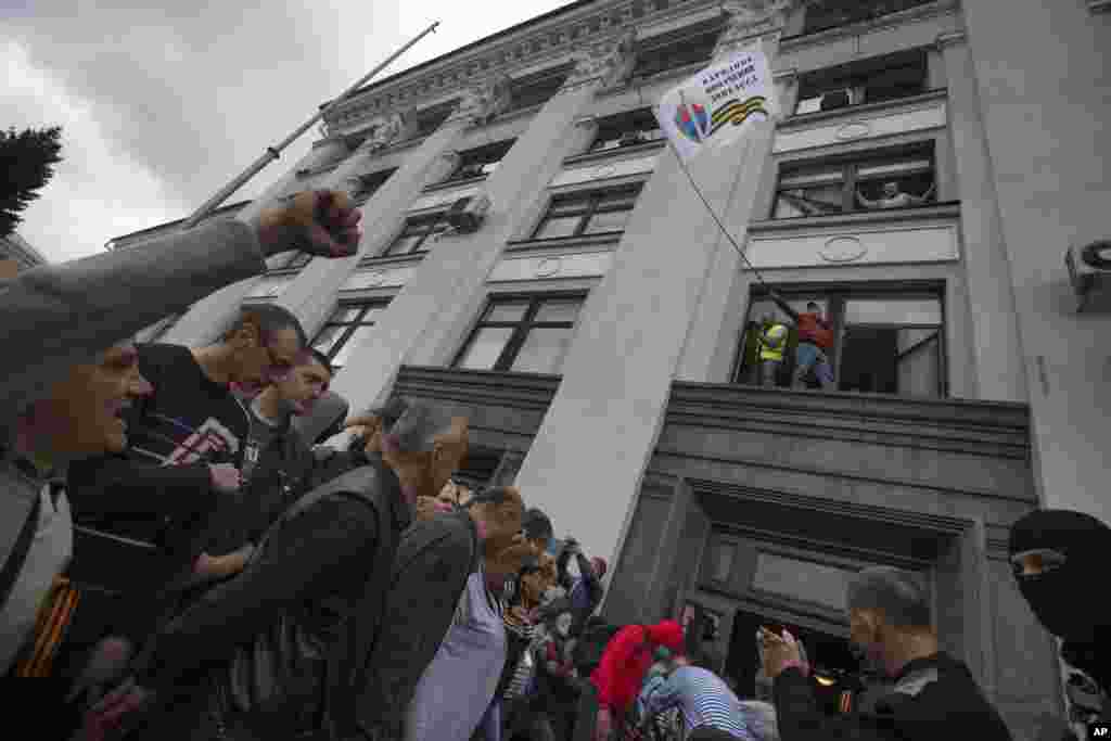 A Pro-Russian activist waves a Donbas Republic flag over a crowd celebrating the capture of an administration building in the center of Luhansk, Ukraine, April 29, 2014.