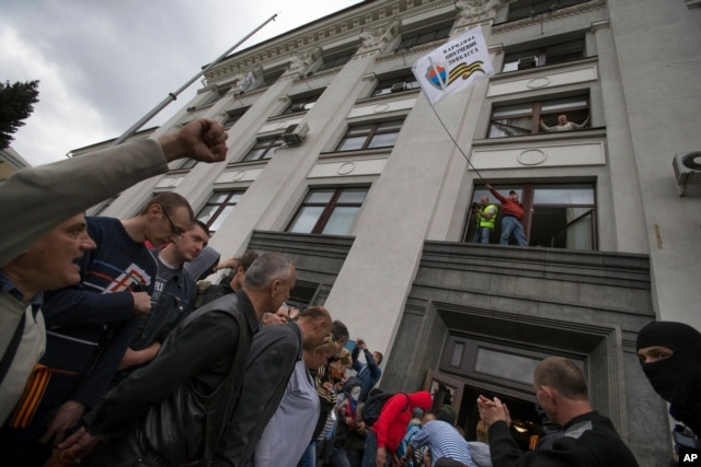 FILE - A Pro-Russian activist waves a Donbas Republic flag over a crowd celebrating the capture of an administration building in the center of Luhansk, Ukraine, April 29, 2014.