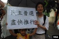 任職律師的香港市民陳先生帶同7歲兒子參加7-1大遊行,爭取盡快普選(美國之音湯惠芸)