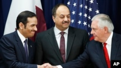 Qatar's Foreign Minister Sheikh Mohammed bin Abdulrahman Al Thani, left, next to Qatar's Defense Minister Khalid bin Mohammad al-Attiyah, shakes hands with Secretary of State Rex Tillerson, right, ‎at the State Department in Washington, Jan. 30, 2018.