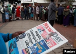 A man reads a newspaper as residents line up to draw money at a bank in Harare, Zimbabwe, Nov. 17, 2017.