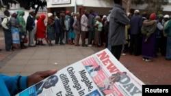 17일 짐바브웨 하라레어 한 남성이 쿠데타 소식이 실린 신문을 읽고 있다. 뒤로 돈을 찾기 위해 은행에 줄을 선 사람들이 보인다.