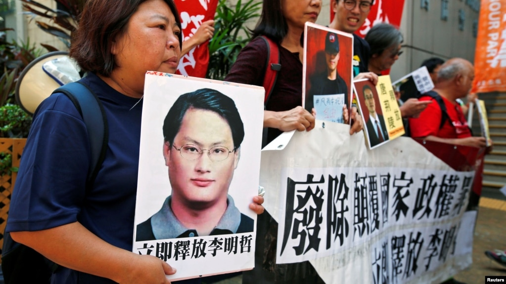 香港民主抗议者举着被拘留的台湾维权活动家李明哲的海报(2017年9月11日)