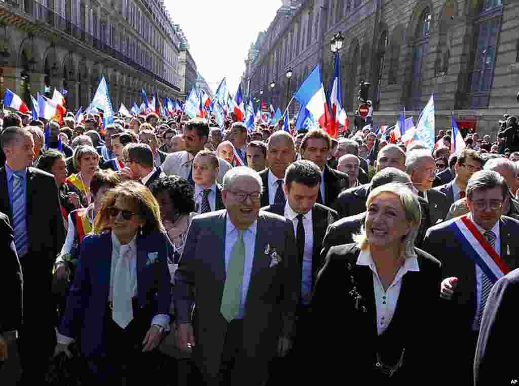 Ứng cử viên Tổng thống của Mặt trận Quốc gia cực hữu Pháp, bà Marine Le Pen, phía tay phải, cùng với bố ông Jean Marie Le Pen đi về phía bức tượng của Joan of Arc, trong cuộc tuần hành truyền thống Ngày Lễ Lao động, tại Paris, ngày 1 tháng 5, 2012. (AP)