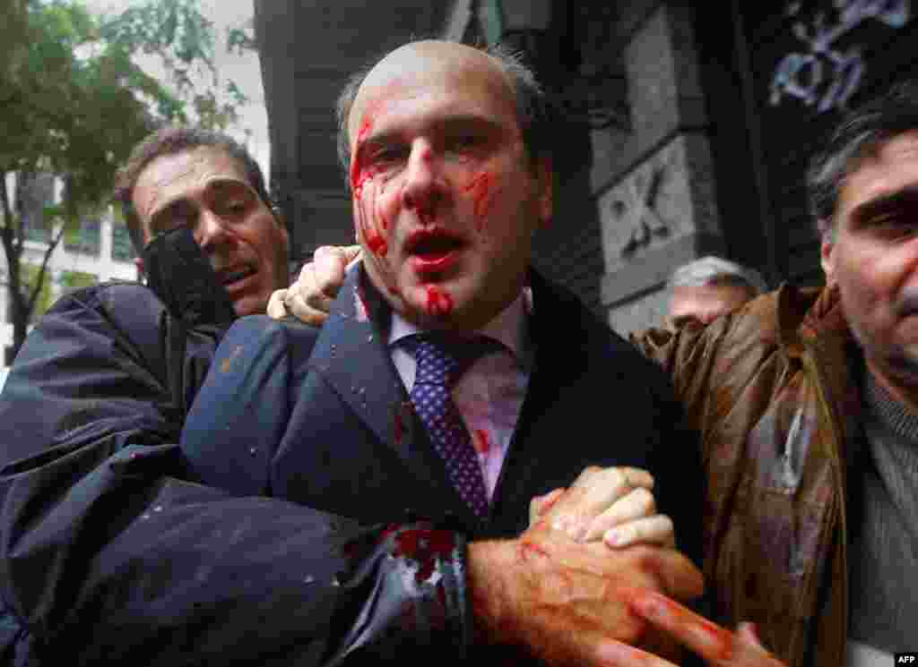 "Former conservative minister of transportation Kostis Hatzidakis is covered with blood after about 200 leftists attacked him with stones and sticks, shouting: ""Thieves! Shame on you!"" in central Athens December 15."