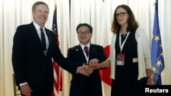U.S. Trade Representative Robert Lighthizer, Japanese Minister of Economy,Trade and Industry Hiroshige Seko and European Commissioner for Trade Cecilia Malmstrom pose for a photo during a meeting at the 11th World Trade Organization's ministerial conferen