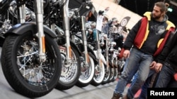 Harley-Davidson bikes are lined up at a bike fair.