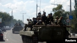 Pro-Russian separatist fighters on armored vehicles in the eastern Ukrainian city of Donetsk, July 10, 2014.
