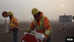 Mike Taylor y Kelly Busby, del estado de Arizona, instalan un punto de control en una carretera cerrada por los incendios en Picnic Hill.