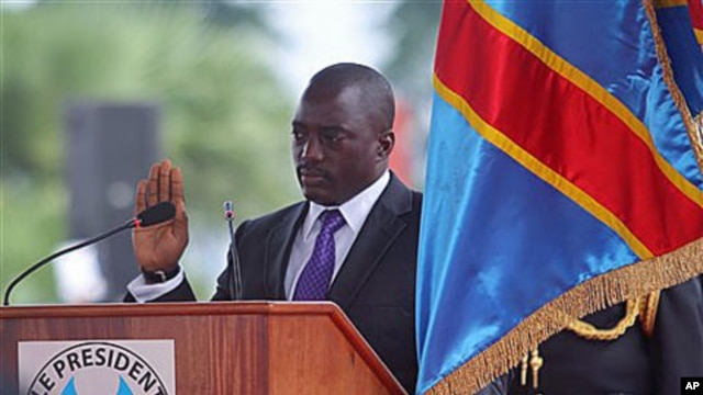 Incumbent Congo President Joseph Kabila holds the Congolese flag as he takes the oath of office as he is sworn in for another term, in Kinshasa, Congo, December 20, 2011.
