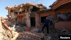 FILE - A Christian man inspects his neighbors' home, destroyed by Islamic State militants in the Christian city of Qaraqosh, Iraq, Sept. 12, 2018.