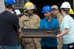 Firefighters and museum personnel carry away a burnt painting from the National Museum after an overnight fire in Rio de Janeiro, Brazil, Sept. 3, 2018.