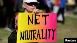 FILE - Lori Erlendsson attends a pro-net neutrality Internet activist rally in the neighborhood where President Barack Obama attended a fundraiser in Los Angeles, California