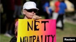 """一位女士在加州參加支持""""網絡中立""""的集會,當時奧巴馬正在附近參加一次募款活動。(2014年7月資料照)"""