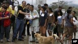 Presiden Filipina Benigno Aquino III (dua dari kiri, barisan depan) membagikan bantuan untuk para korban topan Bopha saat meninjau wilayah New Bataan, Compostela Valley di selatan Filipina (7/12).