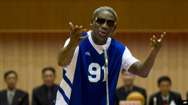 Dennis Rodman sings Happy Birthday to North Korean leader Kim Jong Un, seated above in the stands, before an exhibition basketball game at an indoor stadium in Pyongyang, North Korea, Jan. 8, 2014.
