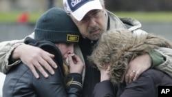 12月16日在康涅狄格州纽敦市桑迪胡克村,人们相拥而泣