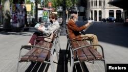 Dos ancianos con mascarillas leen sus periodicos en un parque de Barcelona, España, el 4 de mayo de 2020, tras emitirse un alivio de los confinamientos por el coronavirus.