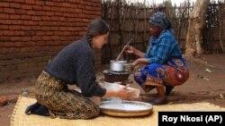 Cameron Beach, left, helps prepare a meal, in Dedza, near Lilongwe, Malawi, Friday, July 23, 2021. (AP Photo/Roy Nkosi)