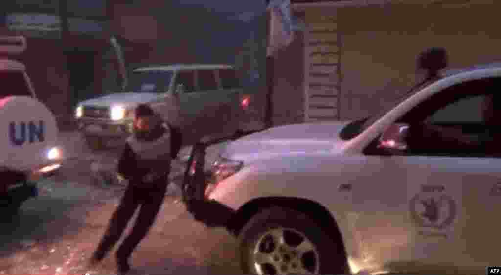 در حالی که خودروهای سازمان ملل و برنامه جهانی غذا گلوله باران می شود، مردی پشت یکی از خودروها پناه می گیرد - هشتم فوریه برگرفته از یوتیوب