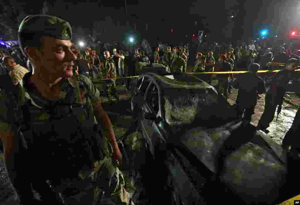 Lebanese soldiers and citizens gather at the site of a car bombing in a southern suburb of Beirut, June 24, 2014.