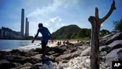 Seorang relawan ikut mengumpulkan gumpalan minyak sawit yang membeku di pantai Pulau Lamma, Hong Kong, Selasa (8/8).