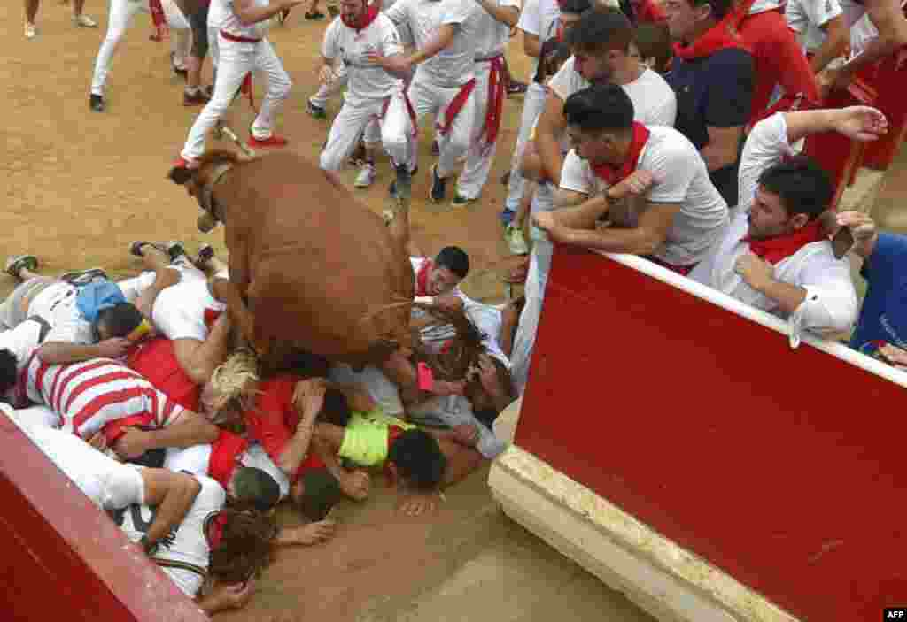 A bull jumps over a crowd of people at the bullring during festivities of the San Fermin festival in Pamplona, northern Spain.