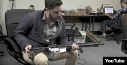 Gun rights activist Cody Wilson, director of Defense Distributed, holds a weapon at his Ghost Gunner factory in Austin, Texas. (YouTube)