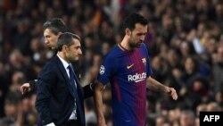 Sergio Busquets discute avec l'entraîneur Ernesto Valverde lors d'un match au Camp Nou de Barcelone, le 14 mars 2018.