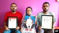 Anindita Mitra, 61, seen with her sons Satyajit Mitra, right and Abhijit Mitra, pose with portraits of her husband, Narayan Mitra, at her house in Silchar, India, Sunday, Sept. 13, 2020. (AP Photo/Joy Roy)