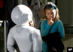 Emerson Hill, 6, seems a bit doubtful as she interacts with Pepper the robot at Westfield Mall in San Francisco, Dec. 22, 2016.