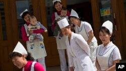 지난해 5월 북한 평양의 한 보육원에서 간호사들이 구호품을 전달하고 돌아가는 유엔과 해외지원기구 관계자들을 배웅하고 있다.