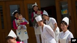 지난해 5월 북한 평양의 한 보육원에서 간호사들이 구호품을 전달하고 돌아가는 국제 구호단체 관계자들을 배웅하고 있다.