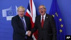 British Prime Minister Boris Johnson shakes hands with European Commission President Jean-Claude Juncker during a press point at EU headquarters in Brussels, Thursday, Oct. 17, 2019.