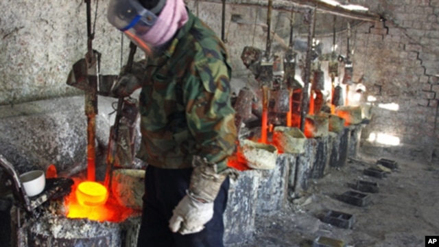 Ren Limin, a worker at the Jinyuan Company's smelting workshop, prepares to pour the rare earth metal Lanthanum into a mold near the town of Damao in China's Inner Mongolia Autonomous Region Oct. 31, 2010.