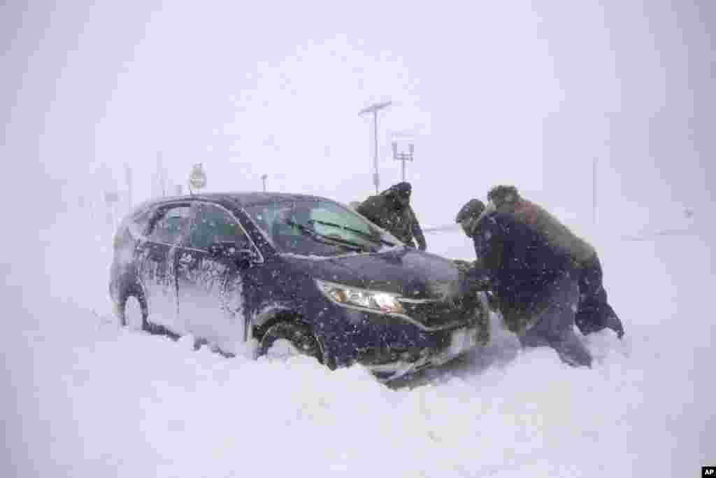 New Jersey'de birkaç kişi, kara gömülmüş bir aracı çıkarmaya çalışıyor .