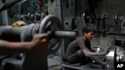 Nizam, 11, works at a factory that makes metal utensils in Dhaka, Bangladesh, June 12, 2016.