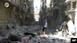 Hình ảnh do nhóm Dân quân Tự vệ Syria cho thấy người dân Syria kiểm tra những tòa nhà bị phá hủy sau các cuộc không kích vào Aleppo, ngày 24 tháng 9 năm 2016.