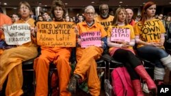 Activists from the antiwar group CodePink hold a silent protest aimed at the Senate Armed Services Committee during a hearing in Washington on the fate of the Guantanamo Bay detention center, Feb. 5, 2015.