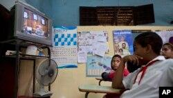 Para pelajar menonton siaran langsung pidato Presiden Kuba Raul Castro mengenai restorasi hubungan dengan Amerika Serikat, dari televisi di sekolah di Havana (17/12). (AP/Ramon Espinosa)