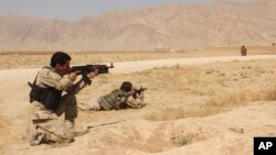 Afghanistan's security forces take their position during a clash by Taliban fighters in the highway between Balkh province to Kunduz city, north of Kabul, Afghanistan, Sept. 1, 2015.