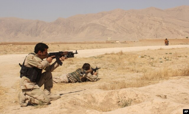 FILE - Afghan security forces clash with Taliban fighters on the highway connecting Balkh province to Kunduz city, north of Kabul, Afghanistan, Sept. 1, 2015.