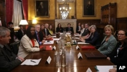 Britain's Prime Minister Theresa May, third left, sits with members of parliament during a meeting to tackle abuse following allegations of sexual harassment and abuse in British politics, at the Prime Minister's Office in the House of Commons, London, N