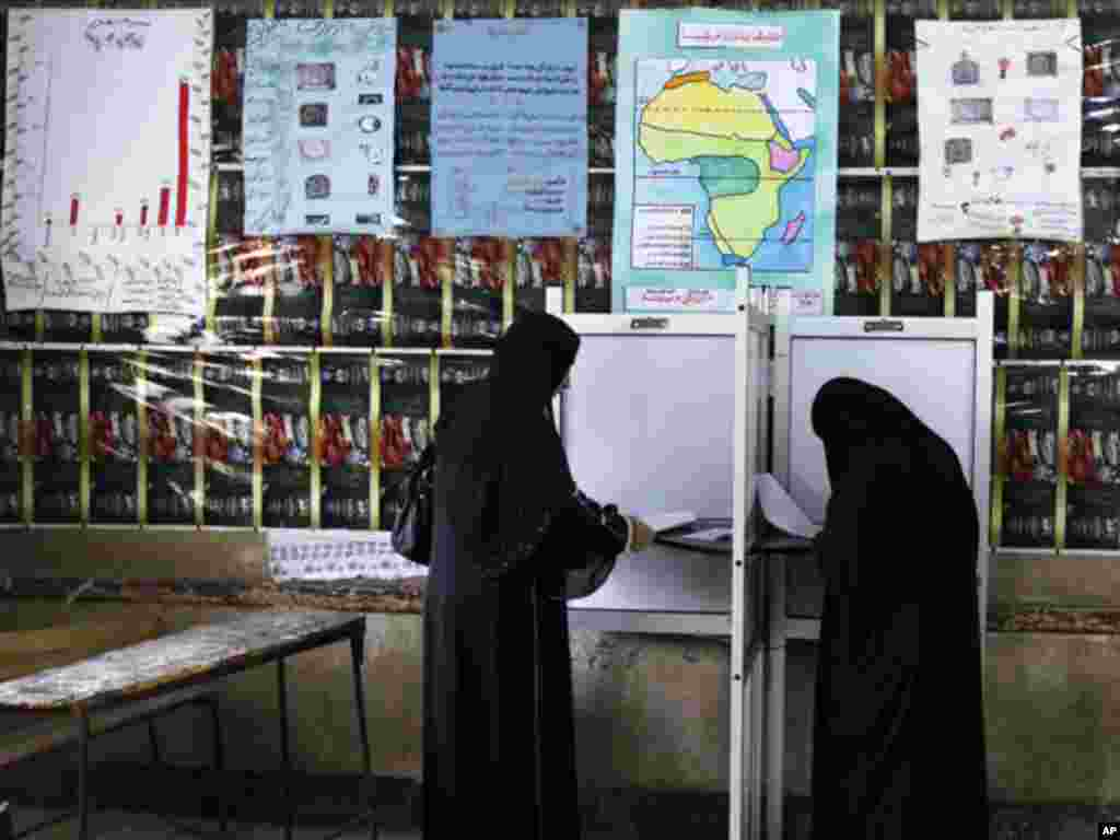 Women read their ballot papers before casting their votes at a polling station at Shubra in El-Kalubia, on the outskirts of Cairo. (Reuters)